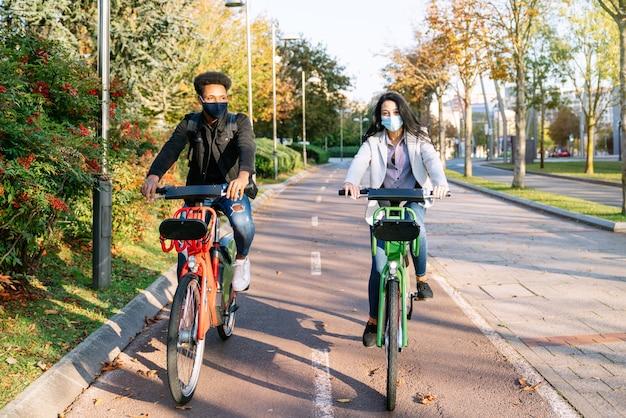 2020 년 코로나 바이러스 전염병에 대한 안면 마스크를 쓰고 석양에 나무가 많은 아름다운 공원에서 공유 전기 자전거를 타고 자전거 길을 타는 두 젊은 남녀의 앞