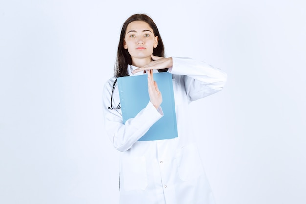 彼女のファイルを保持し、手サインを作る若い女性医師の正面図