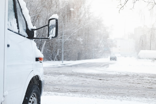 The front part of a car covered in snow. vehicle stands by the snowy road in stormy weather, winter road safety concept