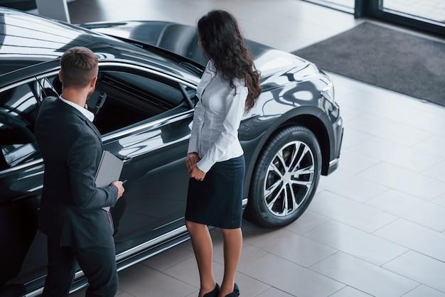 Parte anteriore dell'auto. cliente femminile e uomo d'affari barbuto elegante moderno nel salone dell'automobile