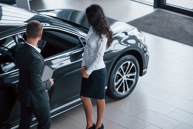 차의 앞 부분. 여성 고객과 자동차 살롱에서 현대적인 세련된 수염 사업가
