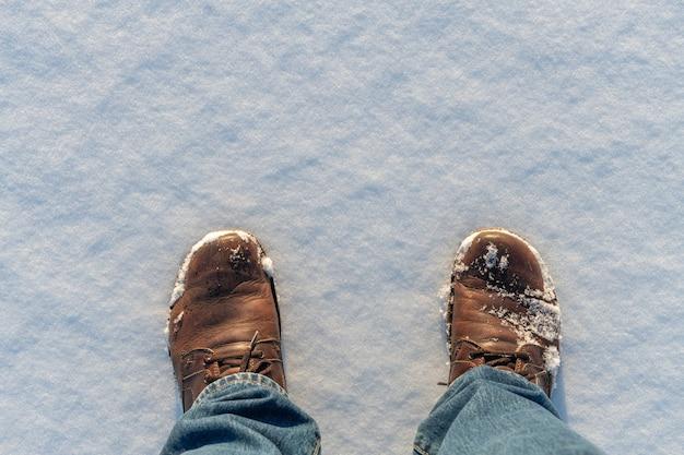 Передние части пары ботинок на белом снегу. вид сверху