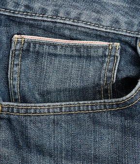 Front pocket of blue classic jeans, full frame, close up
