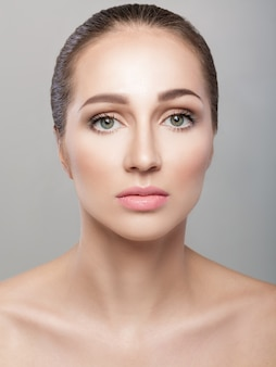 Front portrait of beautiful woman on grey background closeup. girl with clean skin and natural makeup