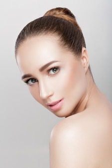 Front portrait of beautiful woman on grey background closeup. girl with clean skin