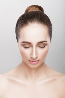 Front portrait of beautiful woman with closed eyes on grey background. girl with clean skin