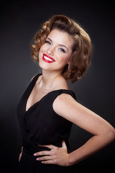 Front portrait of a elegant, smiling young woman, model with charming hairstyle and makeup