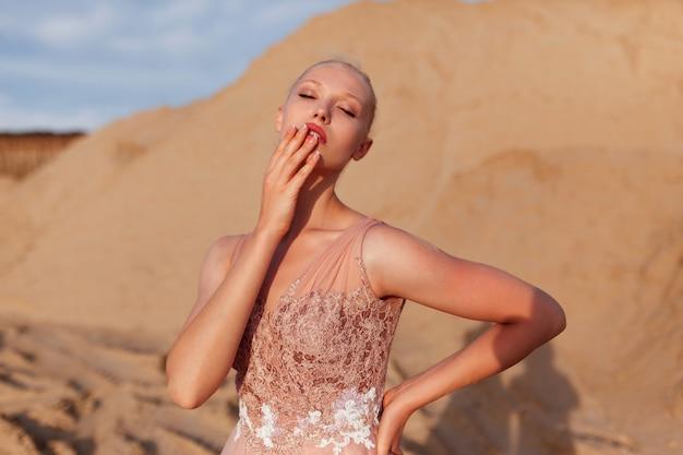 Спереди портрет красивой молодой женщины, позирующей в пустыне, с закрытыми глазами, закрыл лицо рукой. рамка для картины.