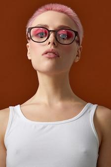 ピンクと眼鏡の短い髪の流行に敏感な若い女性の正面の肖像画