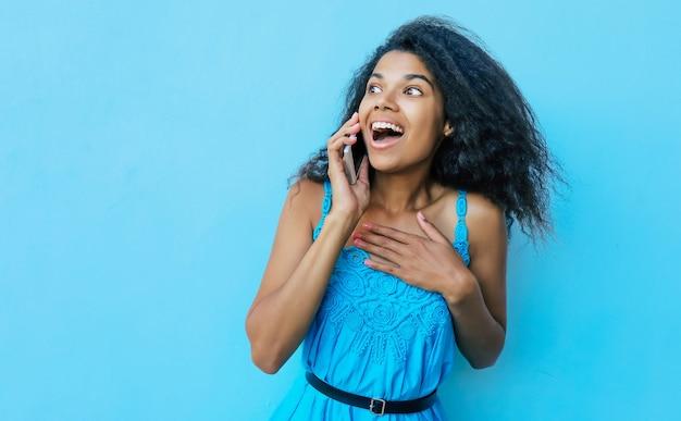 電話で話し、左を見ながら真剣に笑っている、肩までの長さの乱雑な黒髪の楽しいアフリカ系アメリカ人の女の子の正面の肖像画