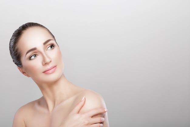 Фронт портрет красивой женщины на сером фоне крупным планом. девушка с чистой кожей