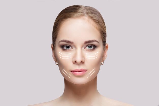 회색 배경 근접 촬영에 녹색 눈을 가진 아름 다운 젊은 금발 여자의 전면 초상화. 깨끗한 피부를 가진 소녀