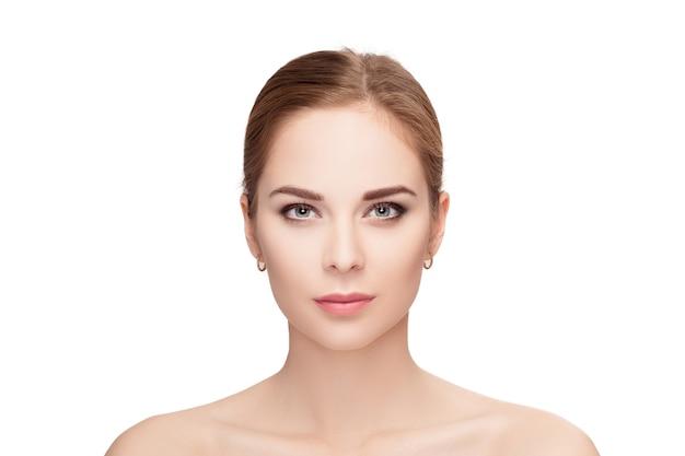 흰색 배경 근접 촬영에 녹색 눈을 가진 아름 다운 젊은 금발 여자의 전면 초상화. 깨끗한 피부를 가진 소녀