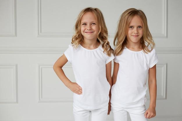 Передний портрет двух маленьких улыбающихся девочек в белой одежде