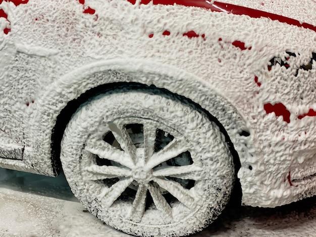 セルフサービスの洗車で車を洗うために泡が塗られている赤い車の右前輪。