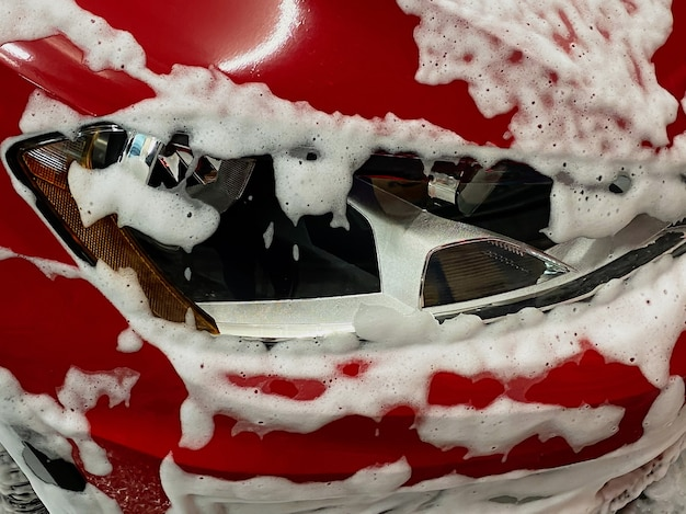 Front right wheel of a red car on which foam is applied to wash a car at a self-service car wash.