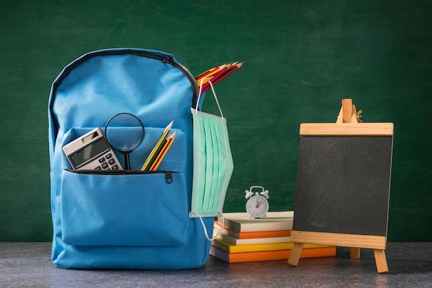 フロントスクールのバックパックとフェイスマスク付きアクセサリーは、緑の黒板の机の上で保護します
