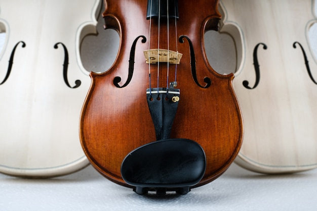Front side of completed violin put at the middle of raw violin