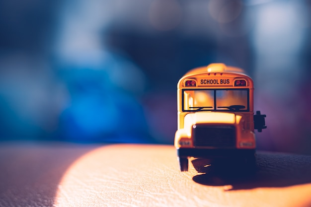 Front side of miniature yellow school bus with sunlight - vintage filter