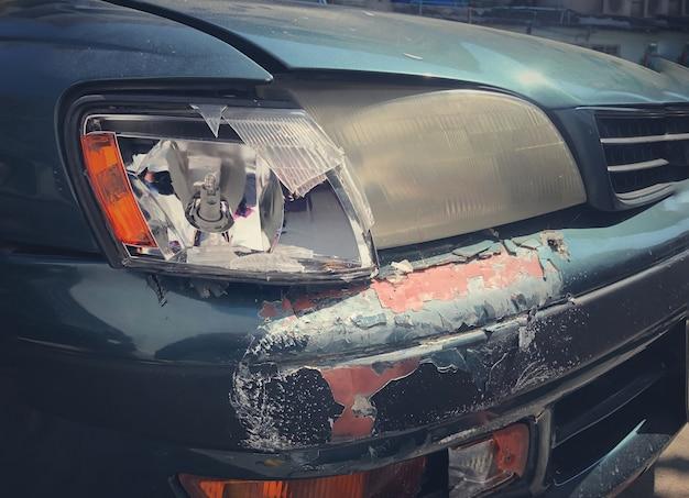 Лицевая сторона автомобиля аварии. автокатастрофа, зеленый автомобиль повредился случайно на дороге, деталь автокатастрофы после аварии с загибом крыла. разбитая фара и потрепанный капот.