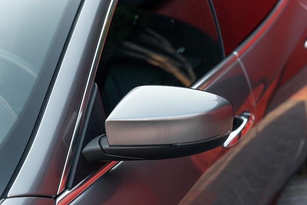 Вид спереди сбоку металлического цвета современного спортивного автомобиля крупным планом внешняя деталь зеркала заднего вида