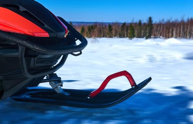 Передняя лыжа снегохода во время езды по заснеженному зимнему пейзажу