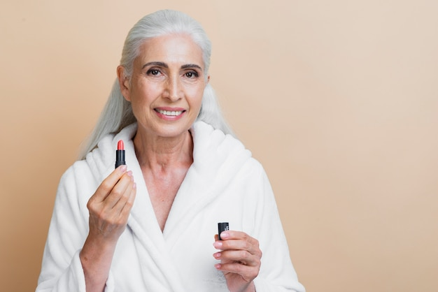 Front smiley woman holding lipstick