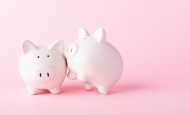 Front two small white fat piggy bank on pink