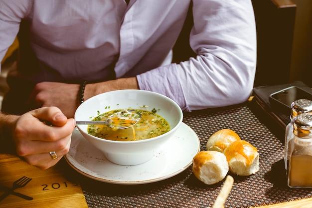 Вид спереди мужчина ест куриный суп с хлебом