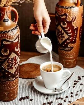 正面の男がコーヒーエスプレッソのカップにクリームを注ぐ
