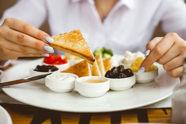Вид спереди женщина завтракает жареными тостами с медовым маслом, сметанным джемом и оливками на тарелке