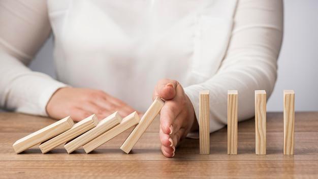 Вид спереди абстрактное представление финансового кризиса с женщиной и деревянными предметами
