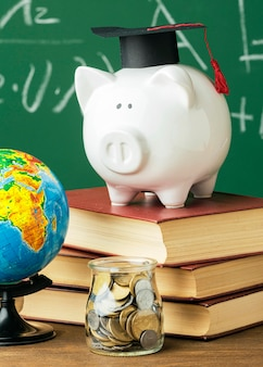Front view of academic cap on piggy bank and stack of books