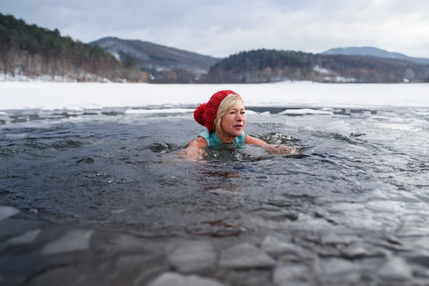 Front view of active senior woman swimming outdoors in water in winter, cold therapy concept.