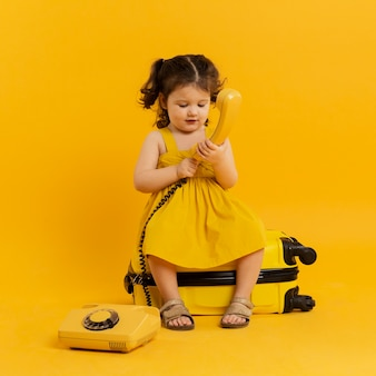 Front view of adorable child posing with telephone and luggage