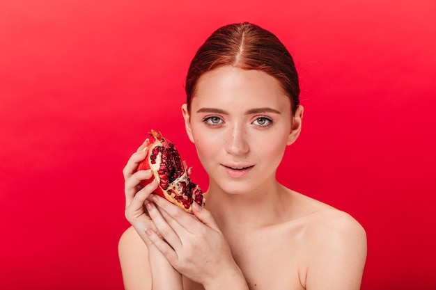 Front view of adorable woman holding ripe garnet. studio shot of ginger naked girl with pomegranate isolated on red background.