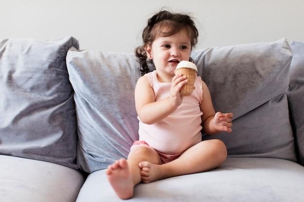 Вид спереди очаровательной молодой девушки на диване
