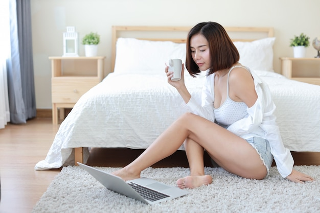 Front view of adult freelance asian woman in white shirt working on computer while drinking coffee or tea in bedroom