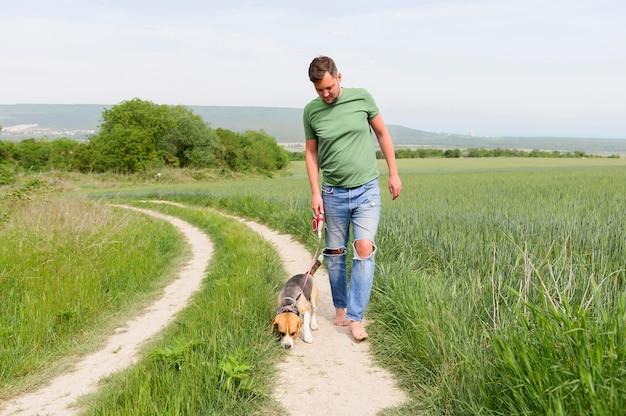 Maschio adulto di vista frontale che va a fare una passeggiata con il suo cane