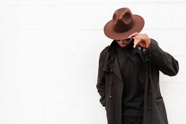 Maschio adulto di vista frontale che posa con il cappello alla moda