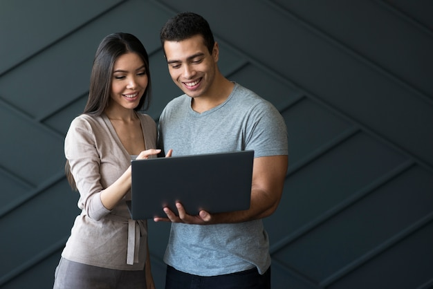 Front view adult male and woman holding a laptop