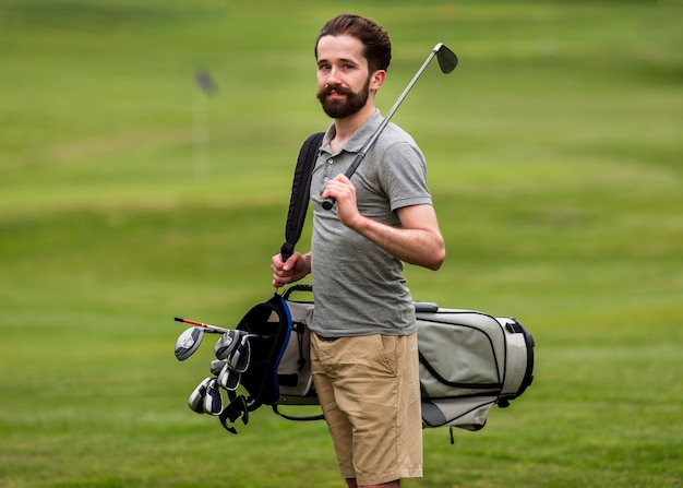 Front view adult man with golf clubs