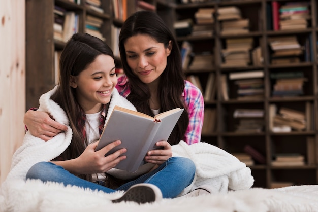 Front view adult woman and girl reading a book