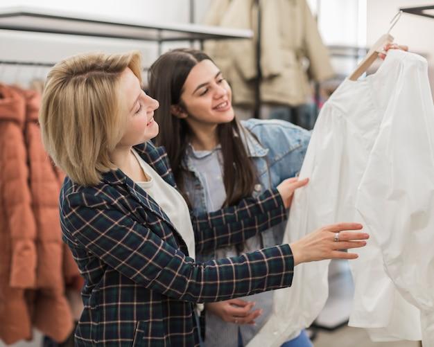 Вид спереди взрослых женщин, проверяющих рубашку