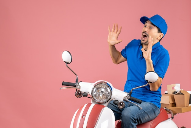 Front view of afraid delivery guy wearing hat sitting on scooter on pastel peach background