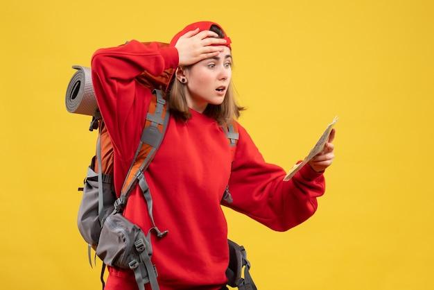 旅行マップを見て正面図の興奮した女性のバックパッカー