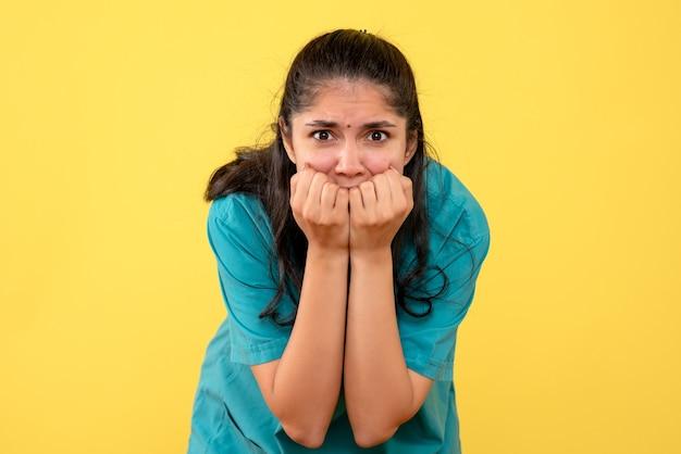 Medico femminile agitato vista frontale in uniforme in piedi su sfondo giallo isolato