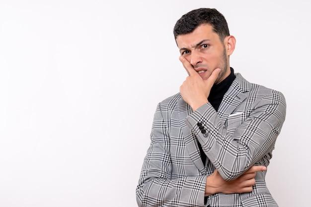 Vista frontale agitato bel maschio in tuta in piedi su sfondo bianco isolato