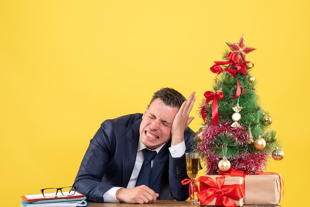 Front view agitated man with closed eyes sitting at the table near xmas tree and gifts on yellow background