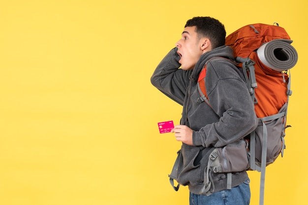 Front view agitated traveler man with red backpack holding discount card